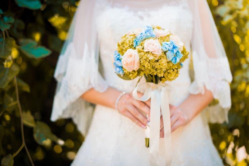 jeune mariée dans une robe se tenant dans un jardin vert et tenant un bouquet de mariage des fleurs et de la verdure photos stock