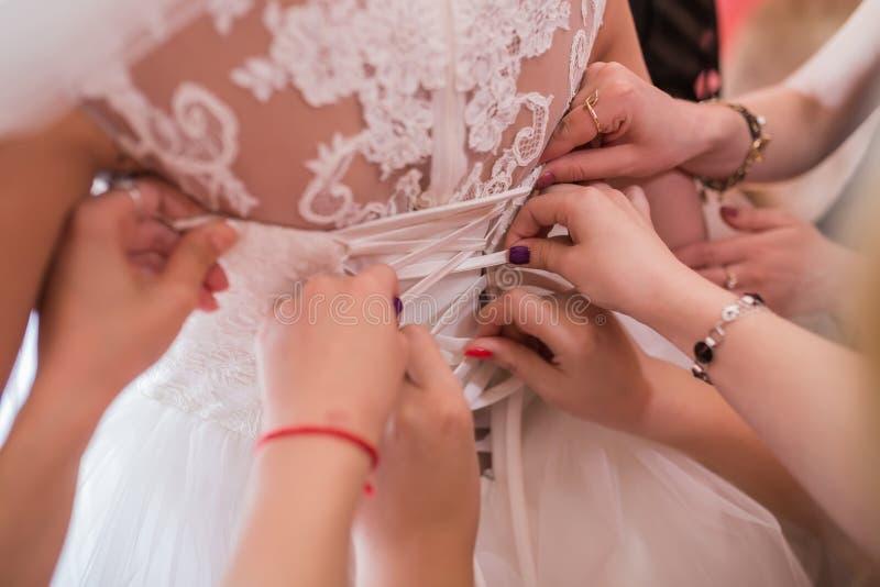 Jeune mariée de aide pour mettre sa robe de mariage dessus image stock