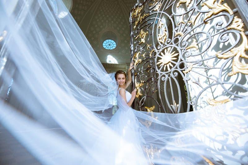 Jeune mariée de beauté dans la robe de mariée avec le voile de bouquet et de dentelle dans la nature photographie stock libre de droits
