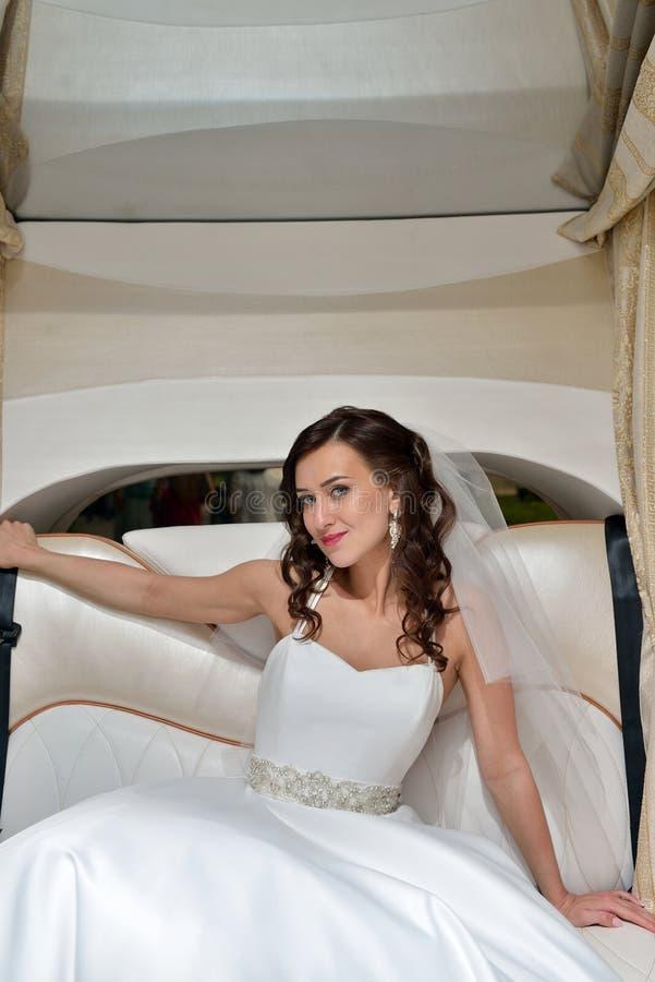 Jeune mariée de beauté dans la robe de mariée avec le voile de dentelle dans la voiture photos stock