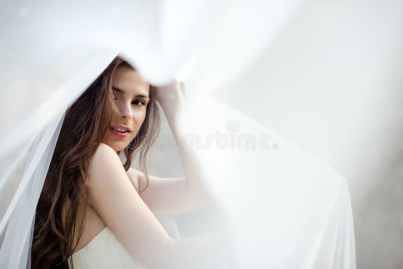 Jeune mariée de brune dans la robe de mariage blanche de mode avec le maquillage images stock