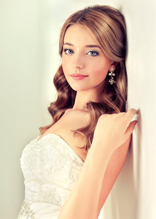 Jeune mariée de fille dans la robe de mariage avec la coiffure élégante photo stock