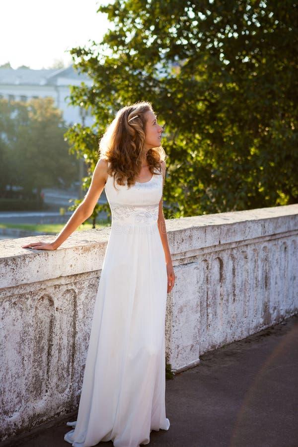 Jeune mariée de jeune fille dans une robe blanche près au vieux marais concret blanc photographie stock