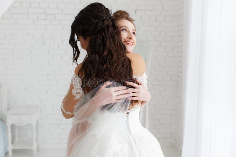 Jeune mariée de luxe étreignant la demoiselle d'honneur et souriant, moment joyeux à l'arrière-plan blanc de brique de grenier mi images libres de droits