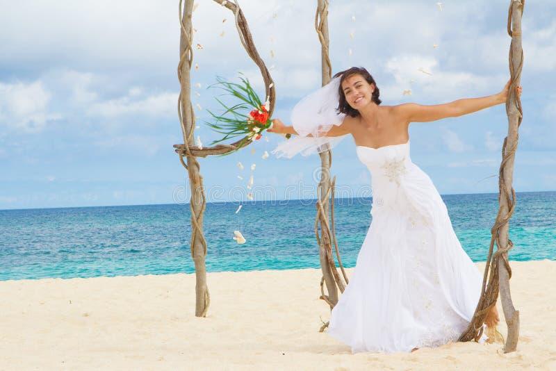 Jeune mariée de sourire heureuse le jour du mariage sur la plage tropicale images libres de droits