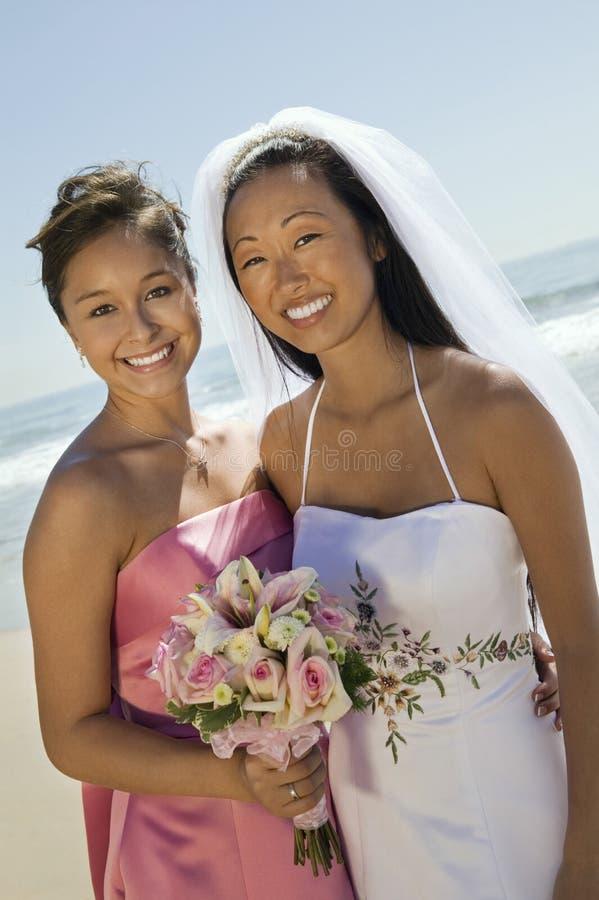 Jeune mariée et demoiselle d'honneur avec le bouquet de fleur souriant sur la plage images stock