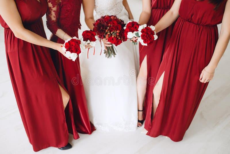 Jeune mariée et demoiselles d'honneur avec les bouquets rouges des roses photo stock