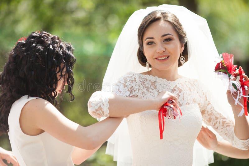 Jeune mariée et demoiselles d'honneur magnifiques élégantes de brune avec le boutonn rouge photos stock