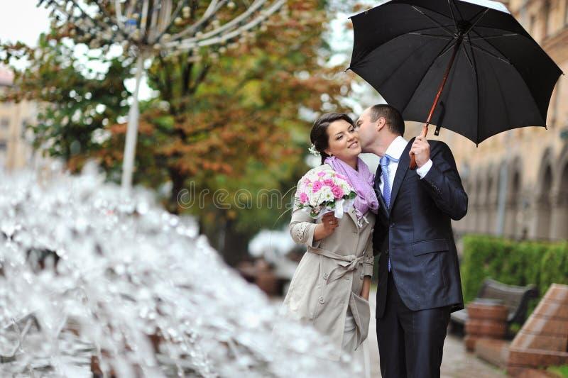 Jeune mariée et marié heureux embrassant par la pluie photos libres de droits