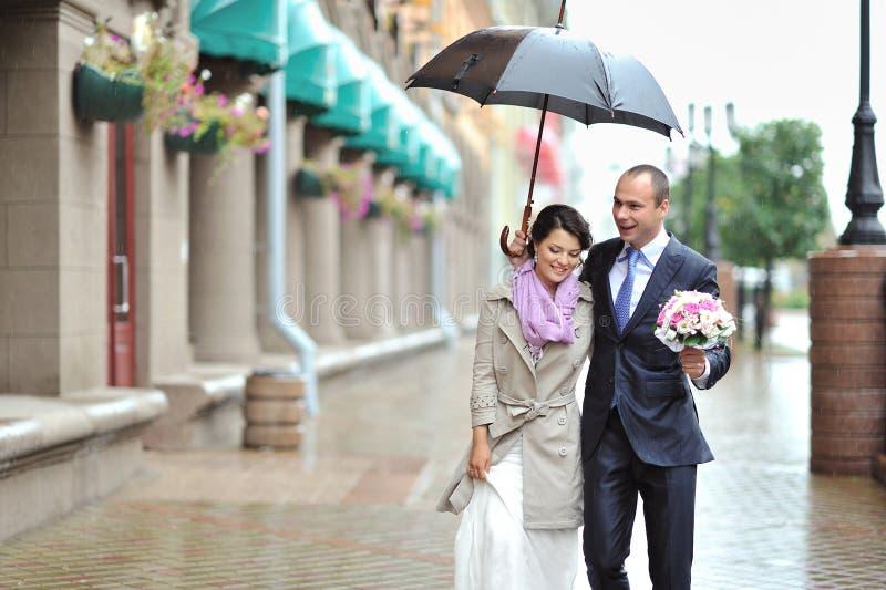 Jeune mariée et marié heureux marchant par la pluie image libre de droits