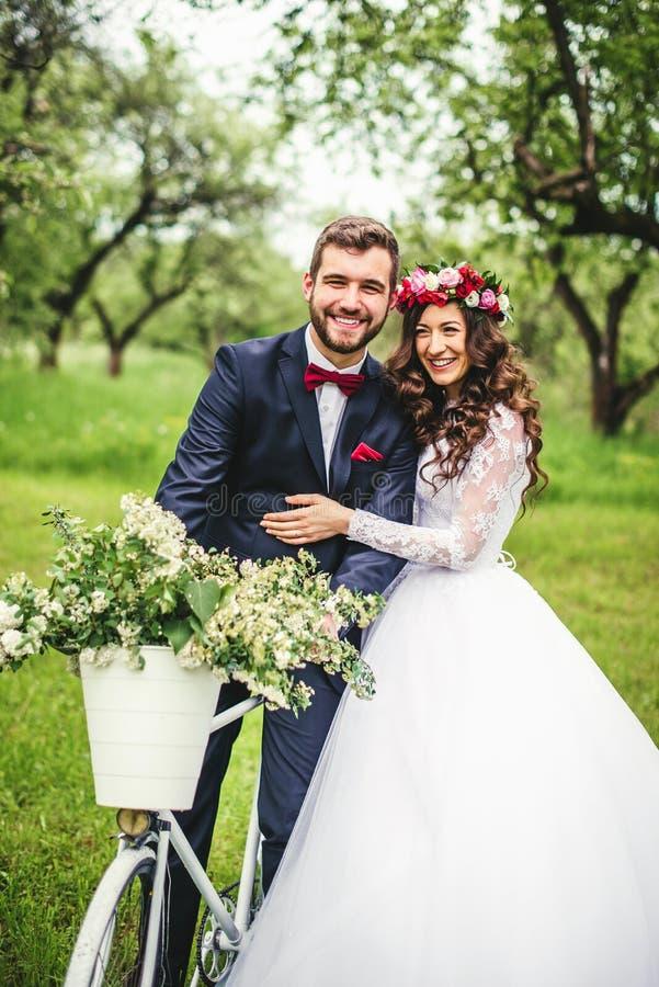 Jeune mariée et marié posant près de la bicyclette photos stock
