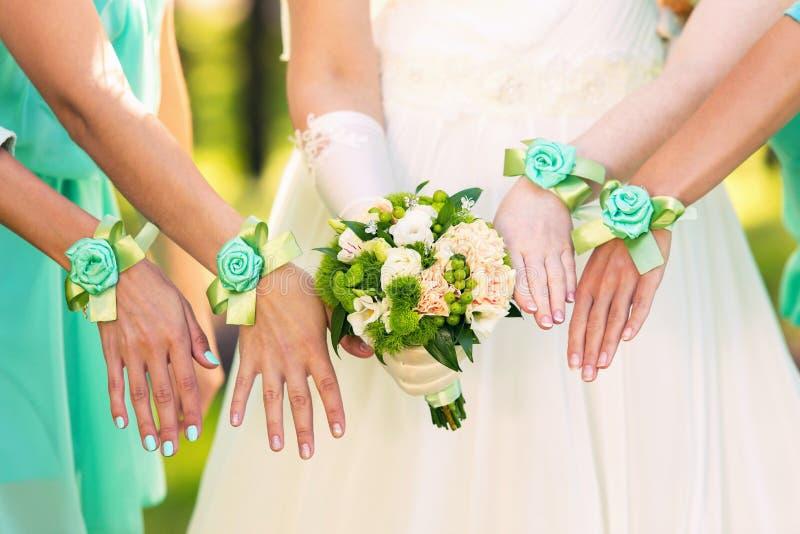 Jeune mariée et ses demoiselles d'honneur avec des bracelets sur des mains photo libre de droits