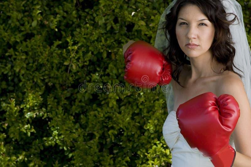 Jeune mariée fâchée dans une robe de mariage et des gants de boxe photos libres de droits