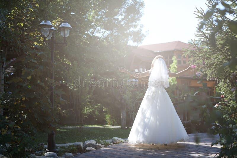 Jeune mariée faisant la pirouette en parc photo stock