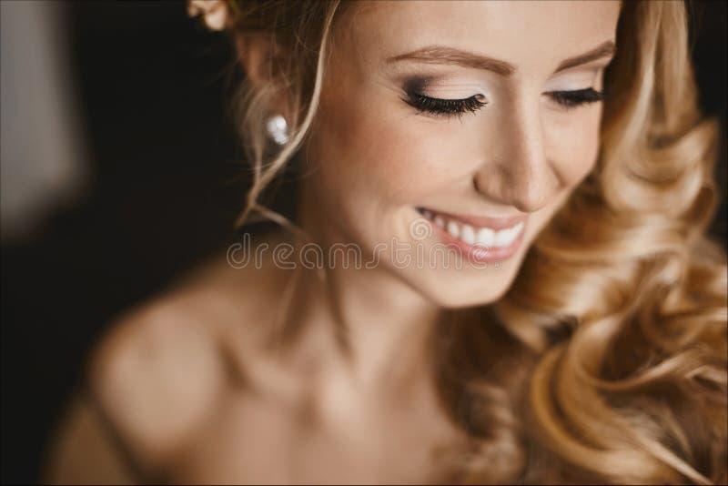 Jeune jeune mariée heureuse avec les yeux fermés et avec la coiffure l'épousant élégante photo stock