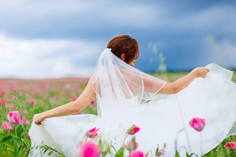 Jeune mariée heureuse dans la robe blanche ayant l'amusement dans le domaine de pavot de fleur image libre de droits