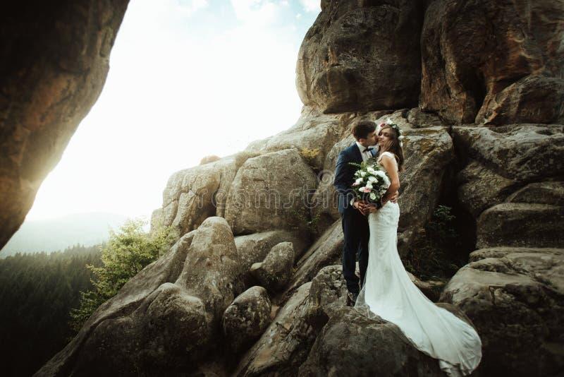Jeune mariée heureuse de luxe et marié élégant embrassant sur le fond du su photographie stock libre de droits
