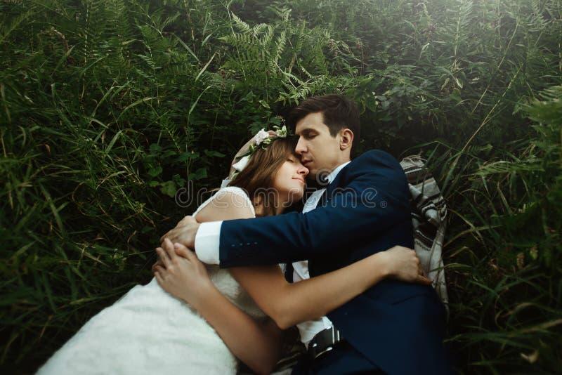 Jeune mariée heureuse de luxe et marié élégant se trouvant sur l'herbe sous ensoleillé photographie stock