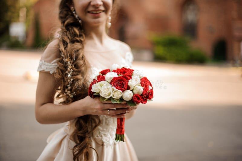 Jeune mariée heureuse de sourire dans une robe l'épousant avec une coiffure de tresse tenant un bouquet des roses images stock