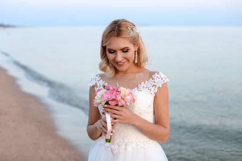 Jeune mariée heureuse tenant le bouquet de mariage photo libre de droits