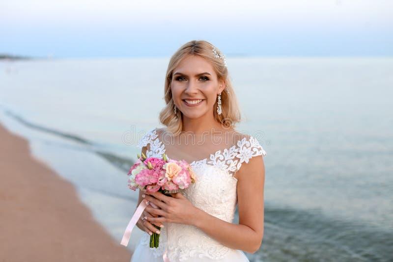 Jeune mariée heureuse tenant le bouquet de mariage photographie stock libre de droits