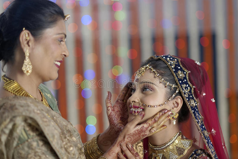 Jeune mariée indoue indienne étant prête avec l'aide de la mère. photo stock