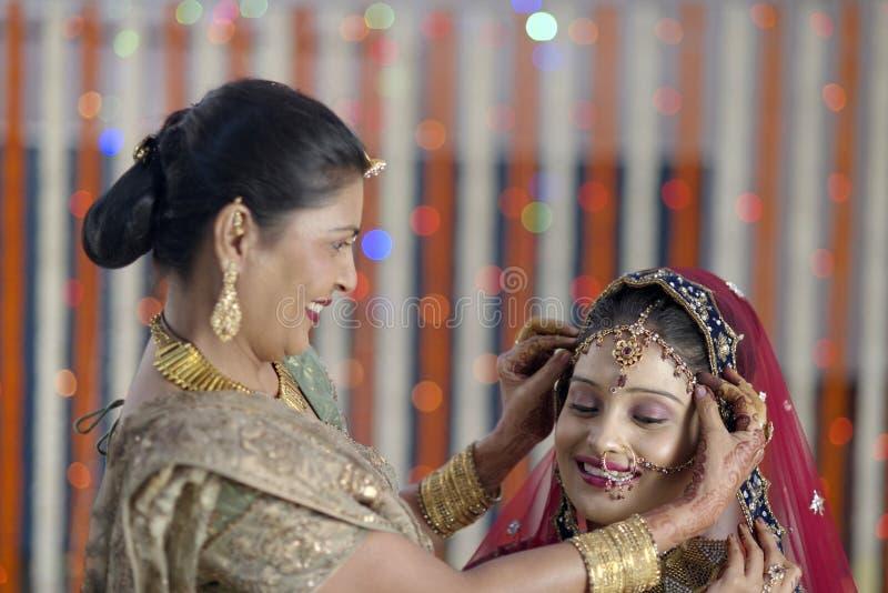 Jeune mariée indoue indienne étant prête avec l'aide de la mère. photographie stock libre de droits
