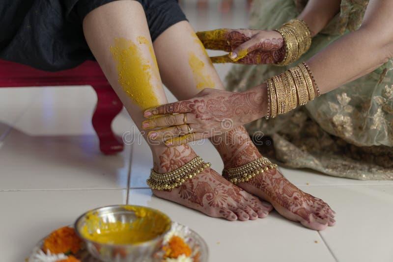 Jeune mariée indoue indienne avec la pâte de safran des indes avec la mère. image libre de droits