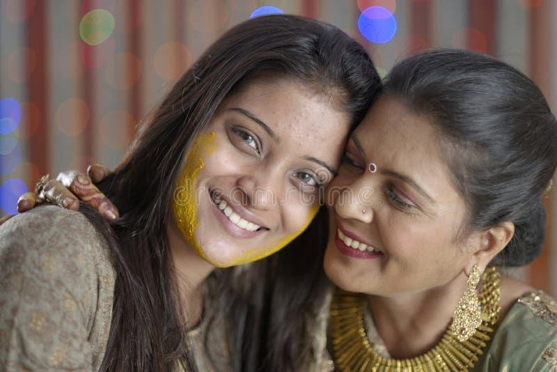 Jeune mariée indoue indienne avec la pâte de safran des indes sur le visage étreignant la mère. photo libre de droits