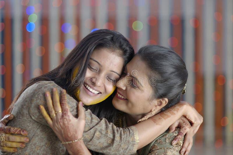 Jeune mariée indoue indienne avec la pâte de safran des indes sur le visage étreignant la mère. photos libres de droits