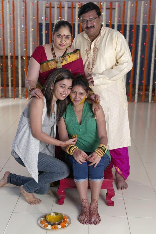 Jeune mariée indoue indienne avec la pâte de safran des indes sur le visage avec la famille. image stock