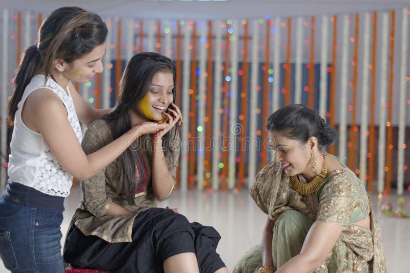 Jeune mariée indoue indienne avec la pâte de safran des indes sur le visage avec la mère et la soeur. image stock