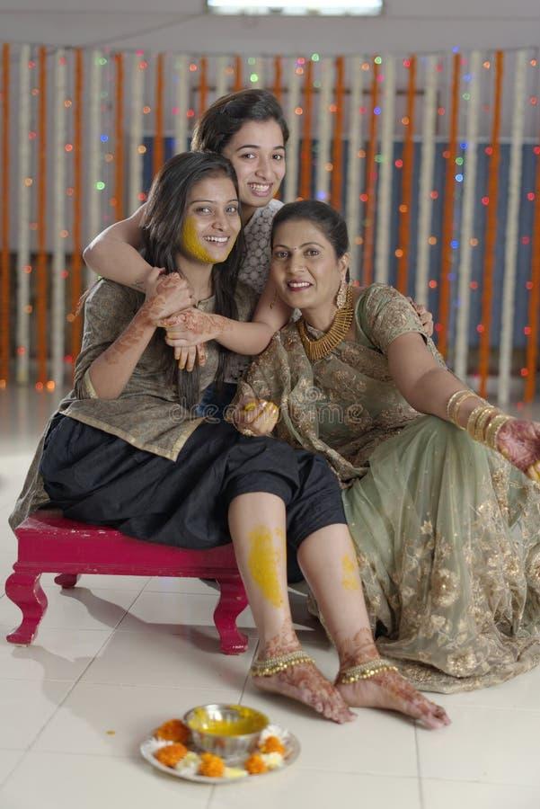 Jeune mariée indoue indienne avec la pâte de safran des indes sur le visage avec la mère et la soeur. photo stock