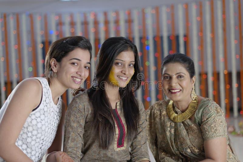 Jeune mariée indoue indienne avec la pâte de safran des indes sur le visage avec la mère et la soeur. photo libre de droits