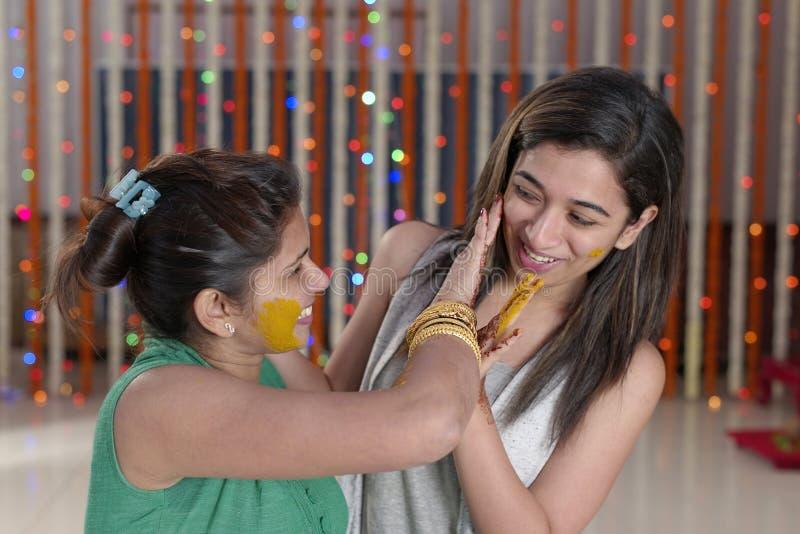 Jeune mariée indoue indienne avec la pâte de safran des indes sur le visage avec la soeur. photo stock