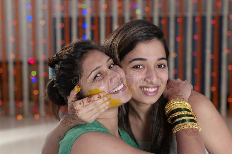 Jeune mariée indoue indienne avec la pâte de safran des indes sur le visage avec la soeur. image libre de droits