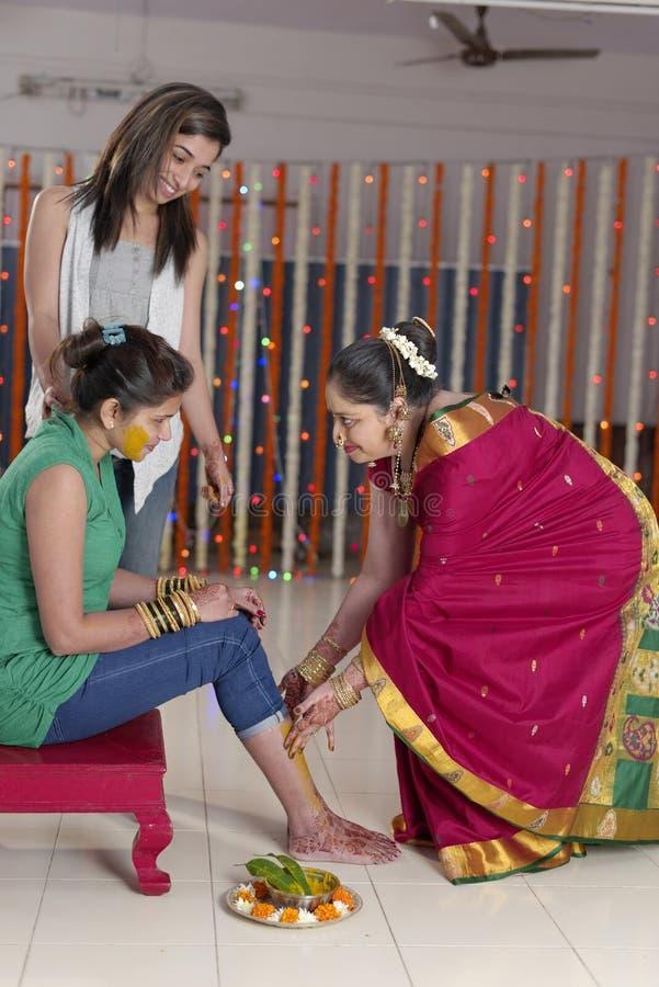 Jeune mariée indoue indienne avec la pâte de safran des indes sur le visage avec la soeur et la mère. photo stock