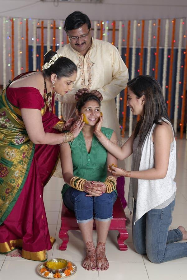 Jeune mariée indoue indienne avec la pâte de safran des indes sur le visage avec la soeur et la mère. images libres de droits