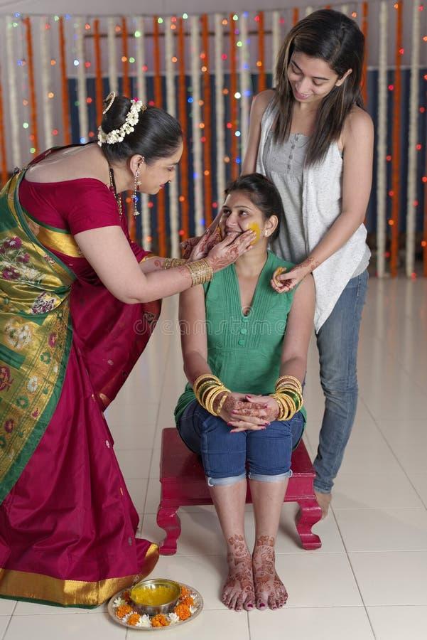 Jeune mariée indoue indienne avec la pâte de safran des indes sur le visage avec la soeur et la mère. photographie stock libre de droits