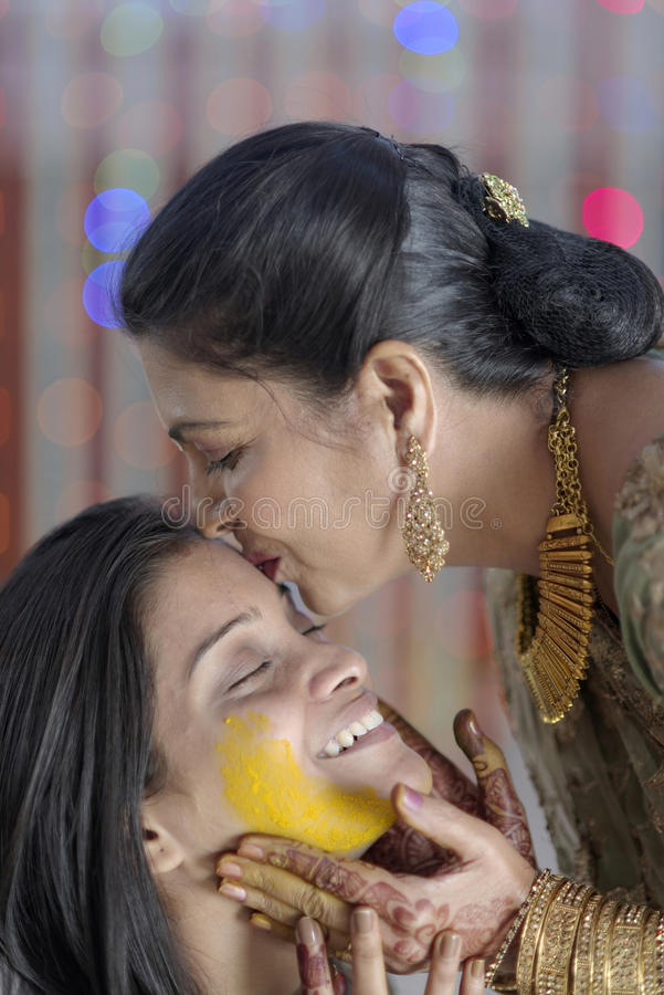 Jeune mariée indoue indienne avec la pâte de safran des indes sur le visage et la mère embrassant la jeune mariée. photographie stock libre de droits
