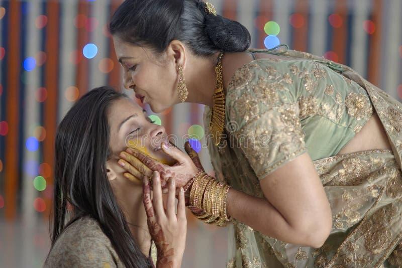 Jeune mariée indoue indienne avec la pâte de safran des indes sur le visage et la mère embrassant la jeune mariée. image libre de droits