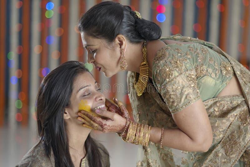 Jeune mariée indoue indienne avec la pâte de safran des indes sur le visage et la mère embrassant la jeune mariée. images libres de droits