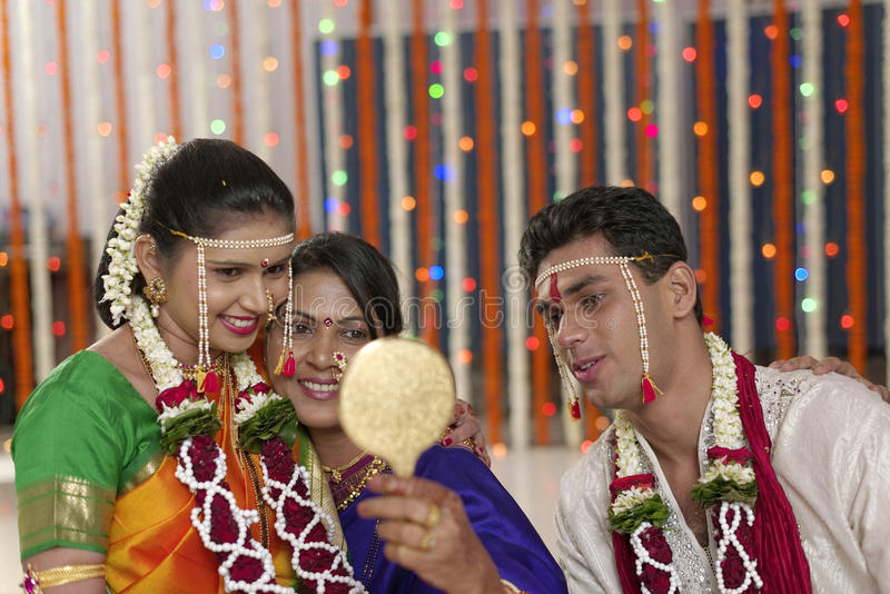 Jeune mariée indoue indienne avec sa belle-mère et marié regardant dans le miroir dans le mariage de maharashtra image stock
