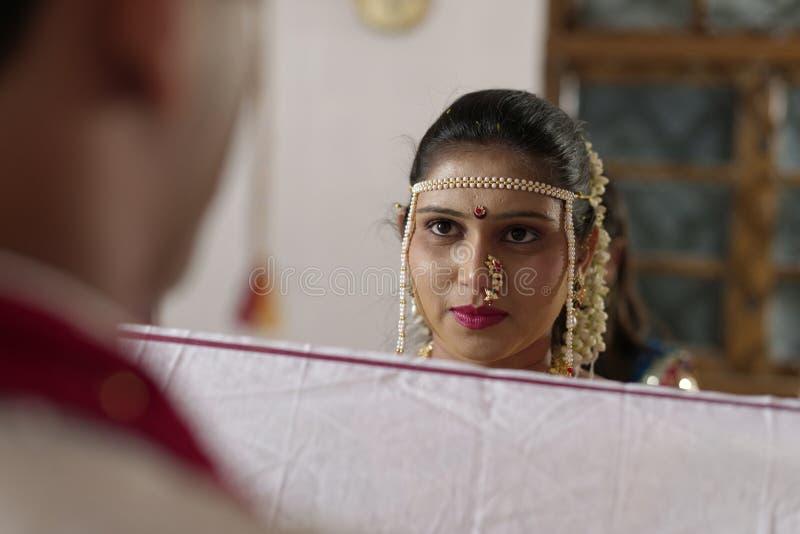 Jeune mariée indoue indienne regardant le marié dans le mariage de maharashtra image libre de droits