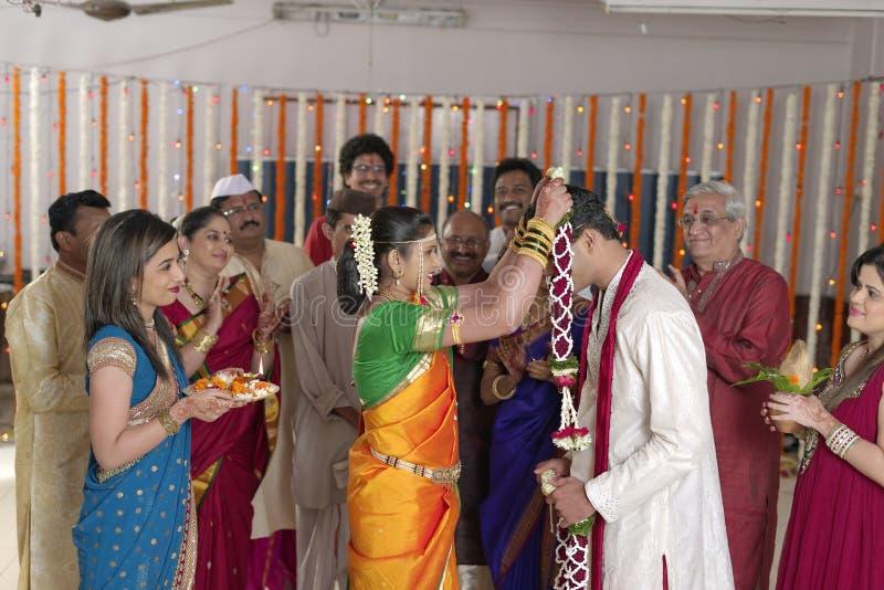 Jeune mariée indoue indienne regardant le marié et échangeant la guirlande dans le mariage de maharashtra image libre de droits