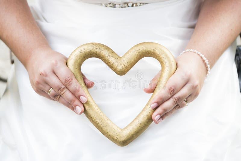 Jeune mariée jugeant le mariage accessoire sous la forme de coeur photos libres de droits