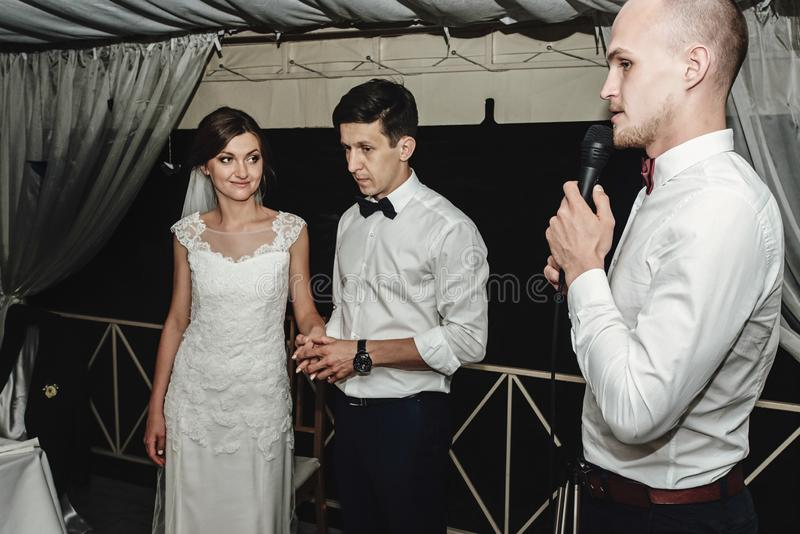 Jeune mariée magnifique élégante et marié élégant avec l'animateur à la réception l'épousant photographie stock