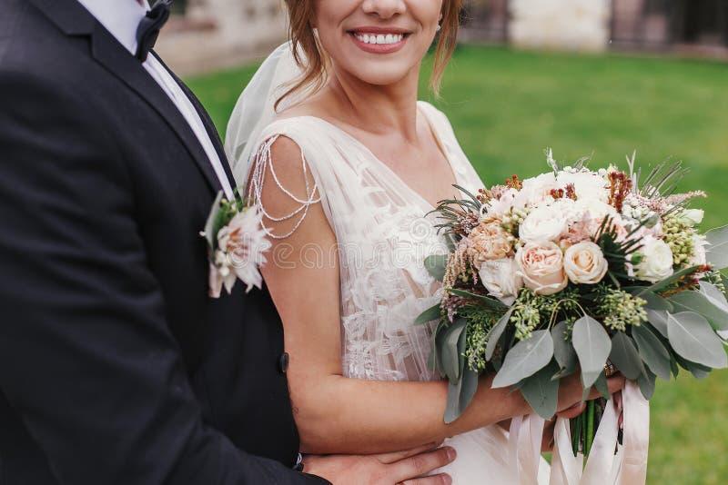 Jeune mariée magnifique avec le bouquet moderne et de marié le hugg élégant doucement photo libre de droits