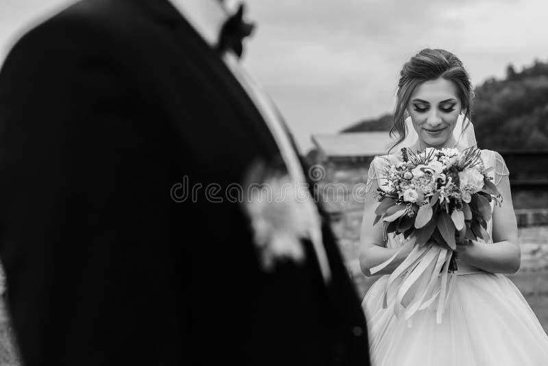 Jeune mariée magnifique avec le bouquet moderne regardant le marié élégant et photos libres de droits