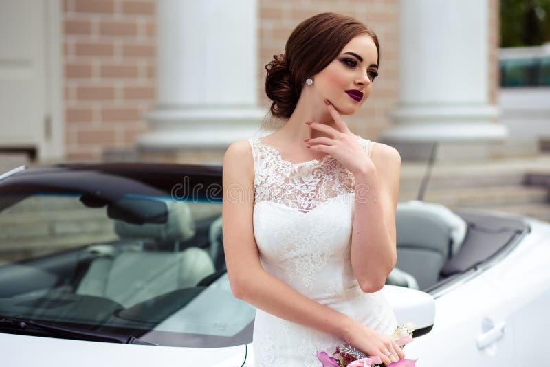 Jeune mariée magnifique avec le maquillage et la coiffure de mode dans une robe de mariage de luxe près de la voiture blanche de  photo stock
